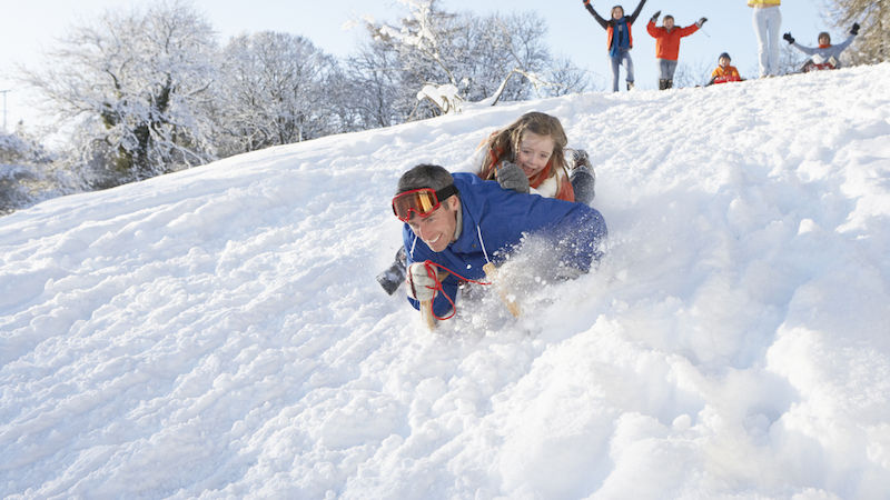Father And Daughter Having Fun Sledging Down Snowy Hill With Family Watching